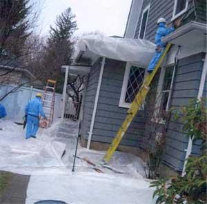 Hazmat suits protect lead abatement specialists during demolition