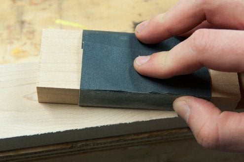 hand sanding with sand paper wrapped around piece of wood