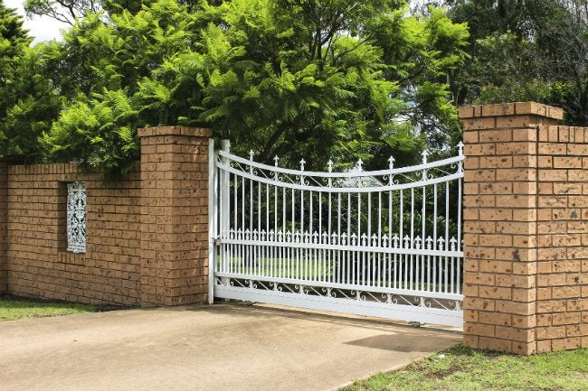 Fence materials pros and cons for 9 top options bob vila for Brick and wrought iron fence designs