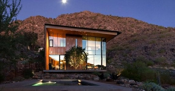 Stunning jarson residence outside view showing exquisite pool on barren landscape surrounded desert vegetations view by night