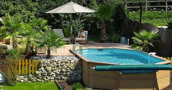 Modern oval above ground pools with decks and outdoor furniture umbrella