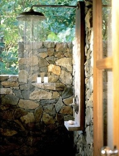 an outdoor shower built with easy access to the house this private extension combines natural rock walls and warm wood tones to give it a zen like appeal