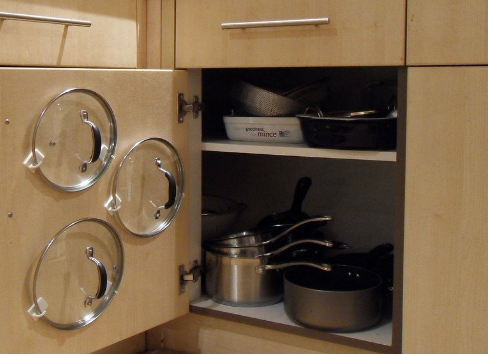 Organize pot pan lids with adhesive hooks