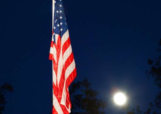 Flying American Flag At Night