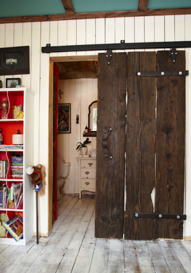 The rustic reclaimed wood used for this sliding door has uneven edges