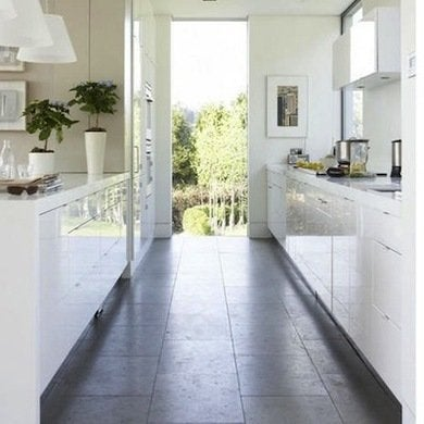 Large Scale Floor Tiles In A Textured Organic Gray Make The Galley Kitchen Design Seem A Lot More Generously